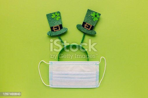 St Patricks Day during coronavirus concept. Headband with hats and mask on green background. COVID-19 quarantine, safe celebration and stay home concept. Top view, flat lay, copy space