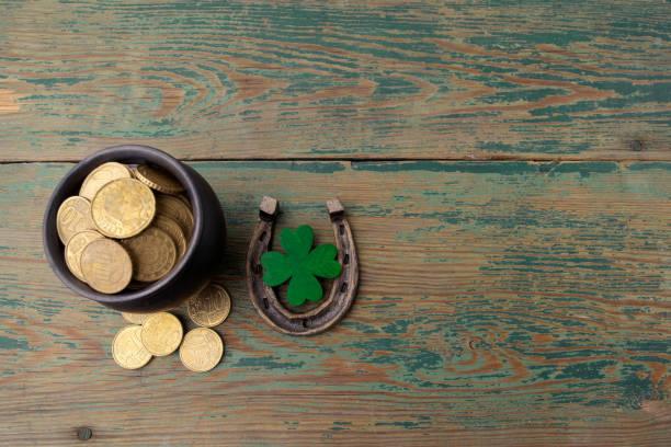 Dia de St. Patricks, amuletos da sorte. Horesechoe e o trevo sobre fundo de madeira - foto de acervo