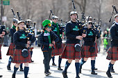 Chicago, Illinois, USA - March 16, 2019: St. Patrick's Day Parade, Bagpipe band wearing White Sox shirts marching down Columbus Drive during the parade