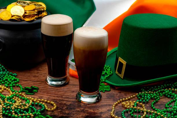 Fiesta del día de San Patricio y celebración irlandesa del tema del concepto de santo patrón con vasos espumosa de hierba seca, sombrero verde con una hebilla, una olla de oro, la bandera de Irlanda y perlas con trébol en un pub - foto de stock
