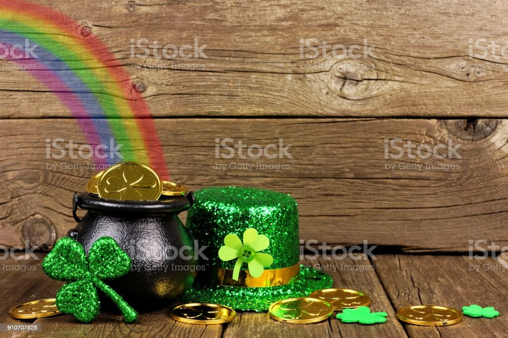 St Patricks Day Pot of Gold with rainbow & decor against wood stock photo