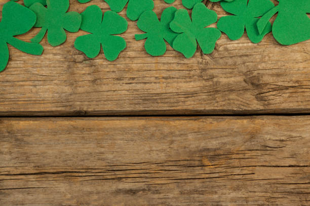 st. patricks day shamrock, beer bottle and pot filled with chocolate gold coins - st patricks day food stock photos and pictures