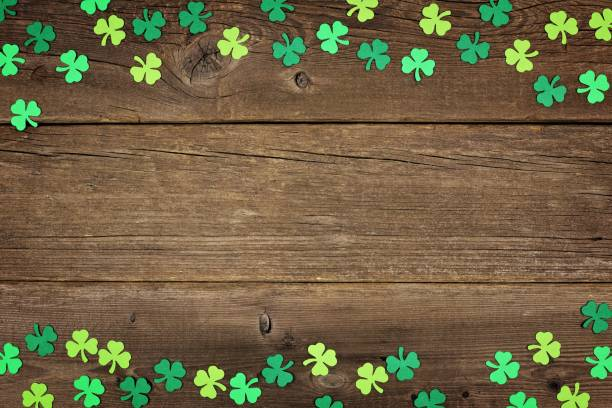 st patricks day shamrocks double border over rustic wood - st patricks day background stock photos and pictures