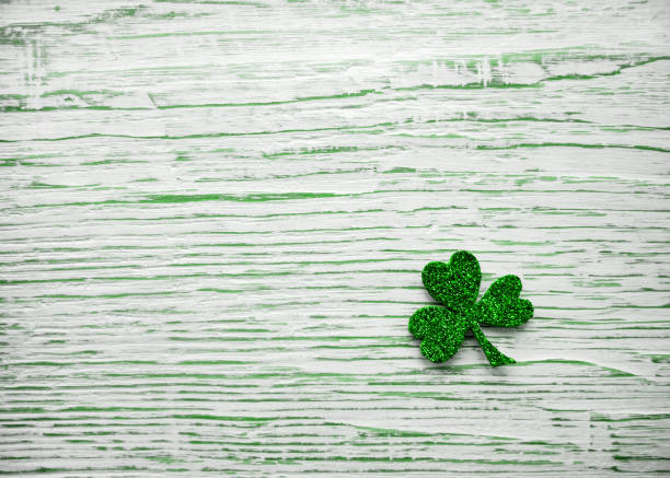 St. Patrick's day. Shiny Shamrock, clover leaf on a light wooden background. St. Patrick's day. Shiny Shamrock, clover leaf on a light wooden background st patricks day stock pictures, royalty-free photos & images