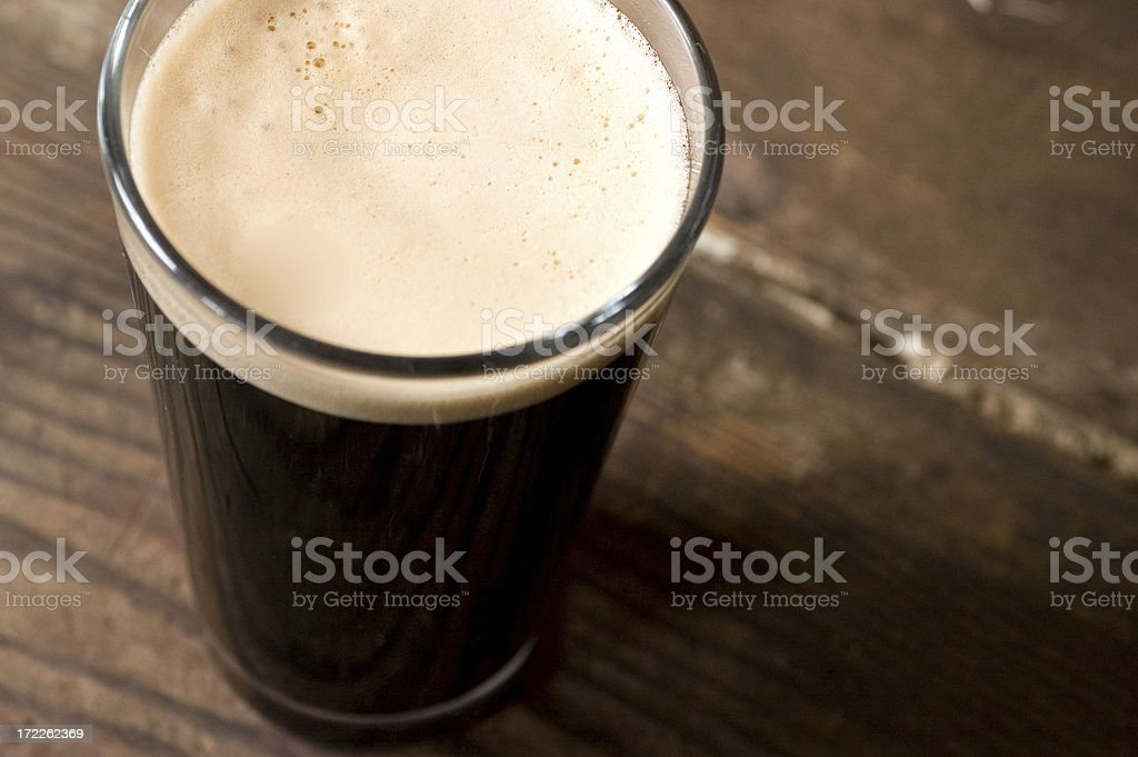 St. Patrick's day stout pint on a wooden surface Tall Cold Stout Alcohol - Drink Stock Photo