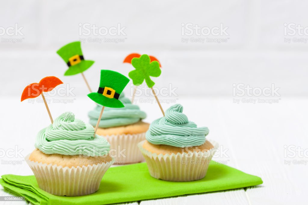 St. Patrick's Day theme colorful horizontal banner. Cupcakes decorated with green buttercream and craft felt decorations in form of leprechaun hat, mustache, shamrock leaves on white background stock photo
