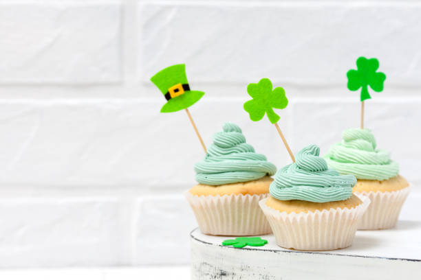 st. patrick's day theme colorful horizontal banner. cupcakes decorated with green buttercream and craft felt decorations in form of leprechaun hat, shamrock leaves on white background. copy space - st patricks day food stock photos and pictures