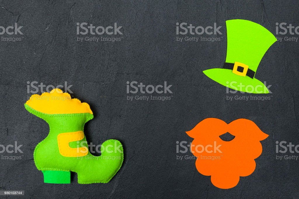 St. Patrick's Day theme colorful horizontal banner. Green leprechaun hat, beard and shoe with gold on black background. Felt craft elements. Copy space. For greeting card, congratulation banner stock photo