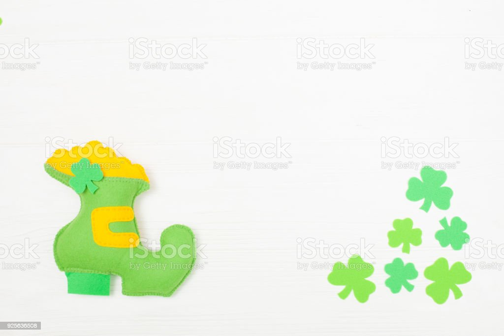 St. Patrick's Day theme colorful horizontal banner. Green leprechaun hand made shoe with gold and shamrock leaves on white wooden background. Felt craft elements. Copy space stock photo