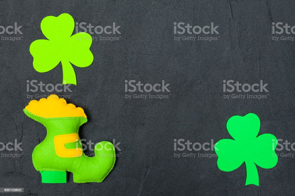St. Patrick's Day theme colorful horizontal banner. Green leprechaun hand made shoe with gold and shamrock leaves on black background. Felt craft elements. Copy space. For greeting card, banner stock photo