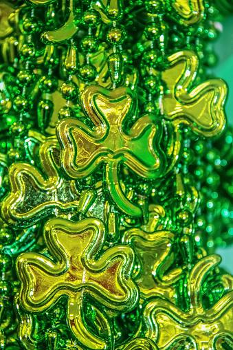 St Patricks Day vertical background of shiny green beads with shamrocks