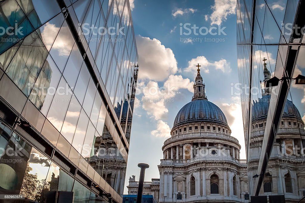 St Paul's cathedral from narrow alley enclosed by glass buildings stock photo