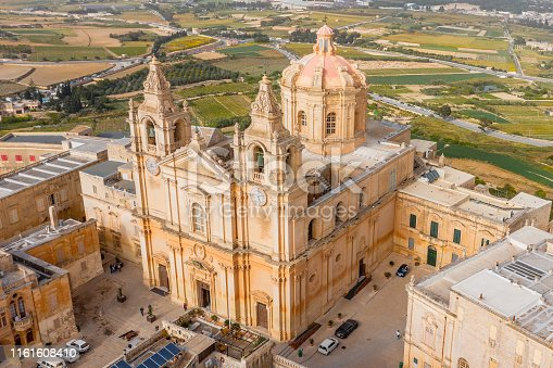 istock St. Paul's Cathedral in the town of Mdina surrounded by a fortress narrow streets, aerial view. 1161608410