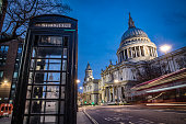 Traditional London telephone booth next to Saint Paul's cathedral in the British capital. Long exposure image with blurred traffic during the early morning hours. Shot on Canon EOS R system with kit lens.