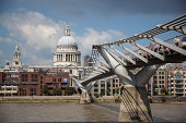 London, United Kingdom - August 25, 2013: View on St Paul's Cathedral  at the distance and Millennium bridge over Thames River. People crossing the bridge.