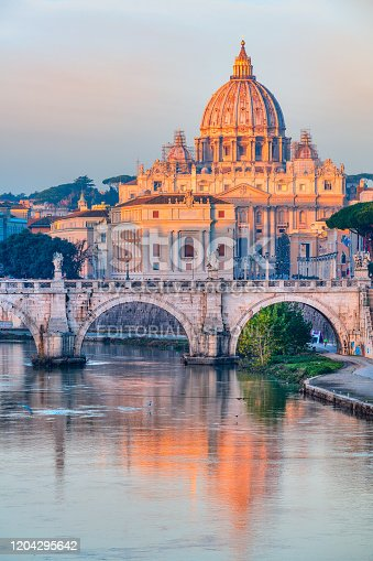 Rome, Italy - February 12, 2018: Sunrise view of St. Peter's Basilica and Sant'Angelo bridge, reflection on Tiber River. Vatican City,  Rome, Italy. Shoot from public bridge Umberto I.