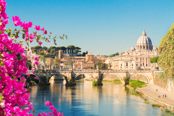 St. Peter's cathedral over bridge St. Peter's cathedral over bridge and river with flowers in Rome, Italy rome italy stock pictures, royalty-free photos & images