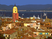 St-Tropez, France - May 5, 2016: This is the fashionable coastal resort of St-Tropez on the Cotes D'Azur, France, Europe. It is a warm sunny day in Spring. This is a view of the old town with the landmark yellow and red church. There are no visible recognisable people in the picture.