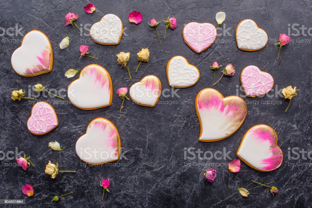 st valentines day arrangement of glazed heart shaped cookies and decorative flowers on dark tabletop stock photo