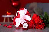 Marry me concept, wedding / engagement ring with red candles, roses bouquet, heart shaped air balloon. Happy st. valentine's day concept. Close up, copy space, front view