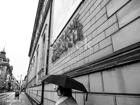 Karlsruhe, Germany - Oct 29, 2017: Staatliche Kunsthalle Karlsruhe State Art Gallery on Hans-Thoma-Strasse street with woman with umbrella on rainy day - black and white