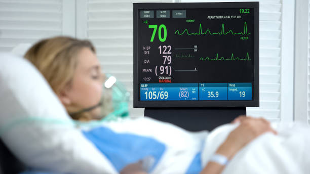 Stabilized woman in oxygen mask sleeping, intensive care hospital unit, surgery stock photo