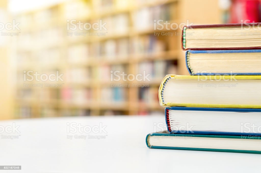Stack and pile of books on table in public or school library. Education, studying and literature service concept with negative copy space. stock photo