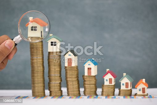 istock Stack coin and bar graph with grow,  Hand hold a magnifying glass searching for a new home, Loan for real estate or save money for buy a house to family in the future concept. 1086887752