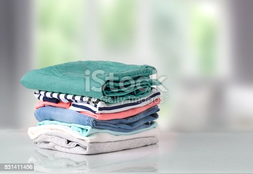 istock Stack colorful cotton clothes on table empty space background. 831411456