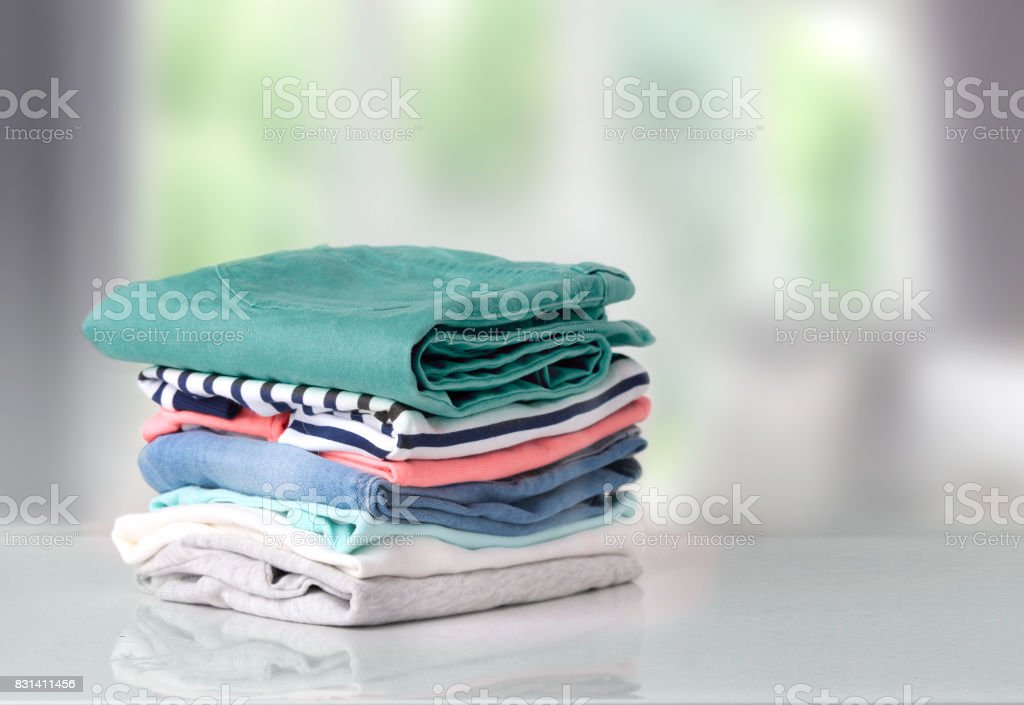 Stack colorful cotton clothes on table empty space background. stock photo