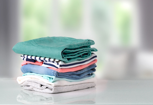 Stack Colorful Cotton Clothes On Table Empty Space Background - zdjęcia stockowe i więcej obrazów Bawełna