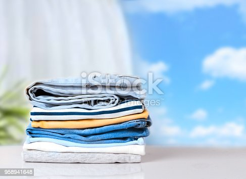 istock Stack cotton clothes on white table empty space background. 958941648