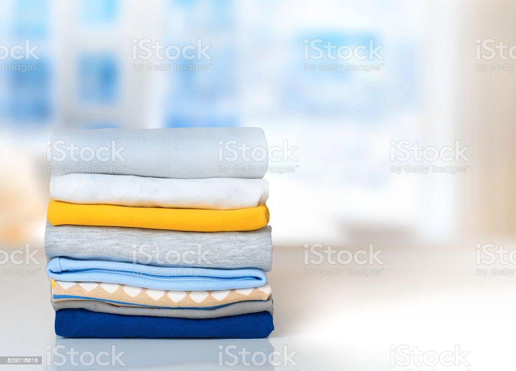 Stack cotton folded clothes on table indoors empty space. - Zbiór zdjęć royalty-free (Bawełna)