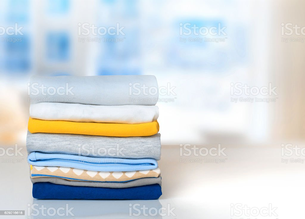 Stack cotton folded clothes on table indoors empty space.