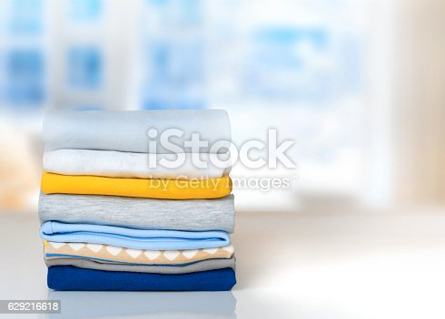 istock Stack cotton folded clothes on table indoors empty space. 629216618