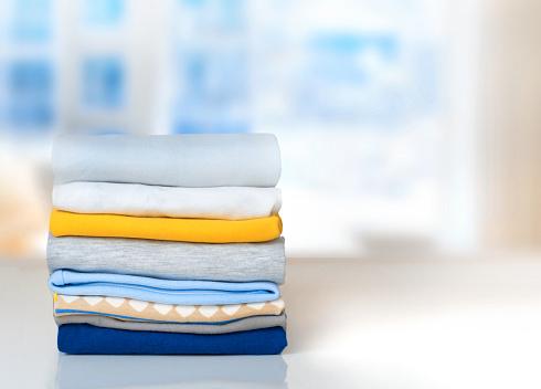 Stack Cotton Folded Clothes On Table Indoors Empty Space - zdjęcia stockowe i więcej obrazów Bawełna