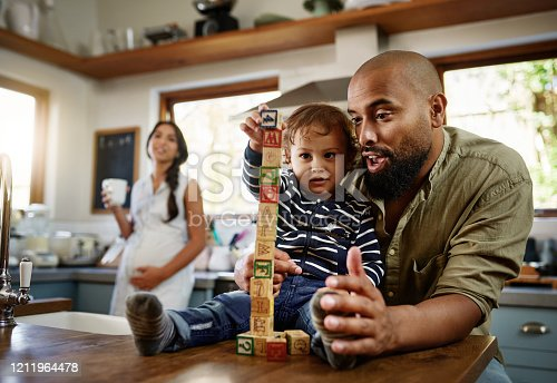 Shot of a young man and his adorable child playing with building blocks together at home