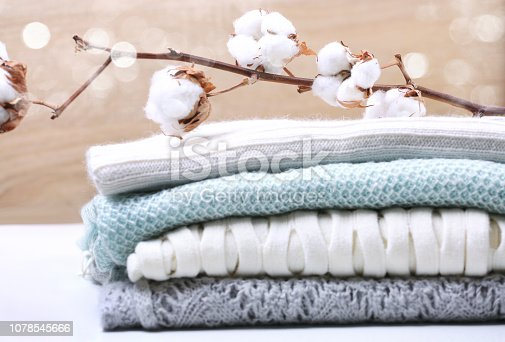 Stack  knitted clothes with cotton flower branch,woolen clothing.Pile of winter sweaters pastel colored.