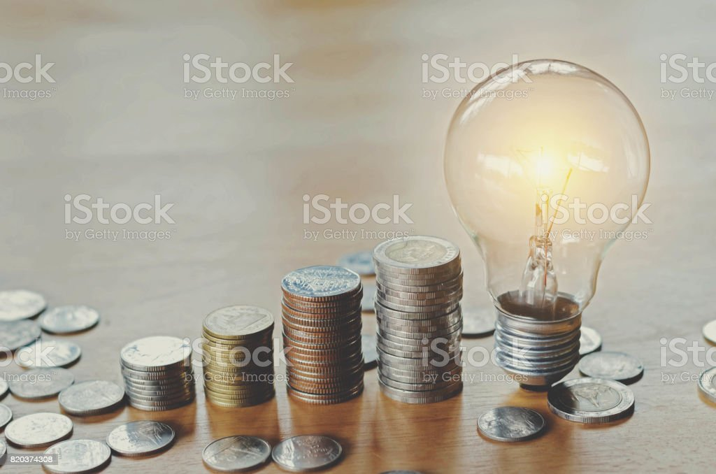 stack money coins with growing light bulb concept stock photo