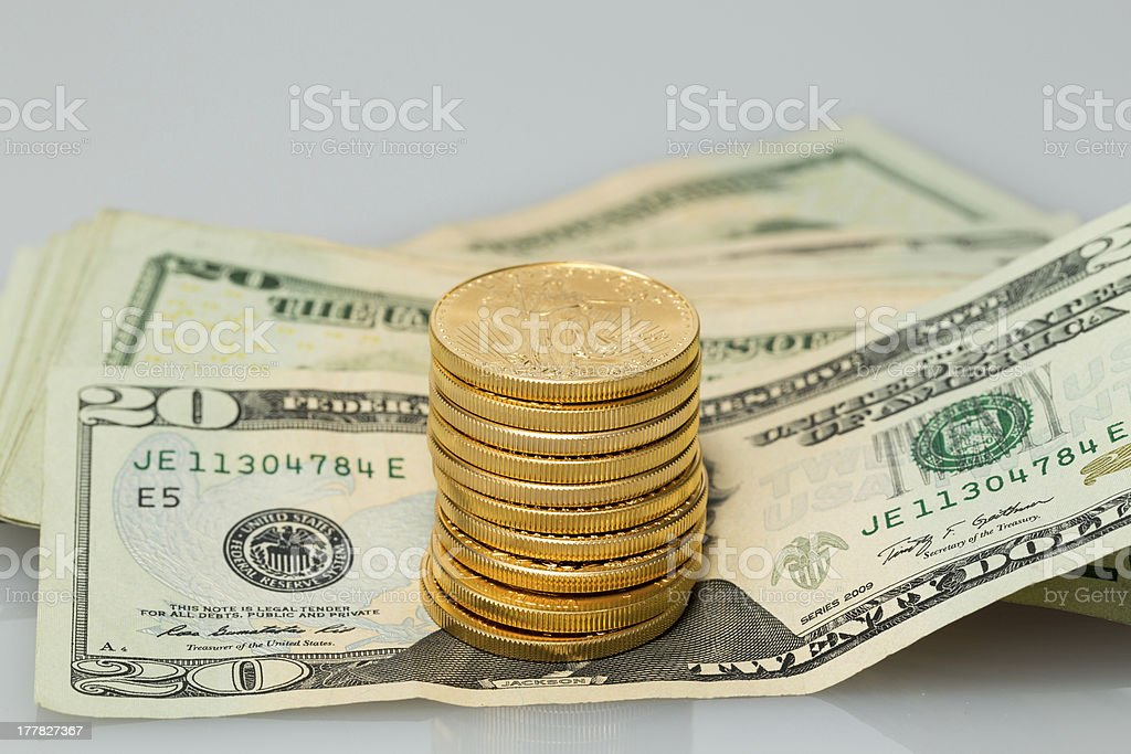 Stack of $20 dollar bills with gold coins royalty-free stock photo