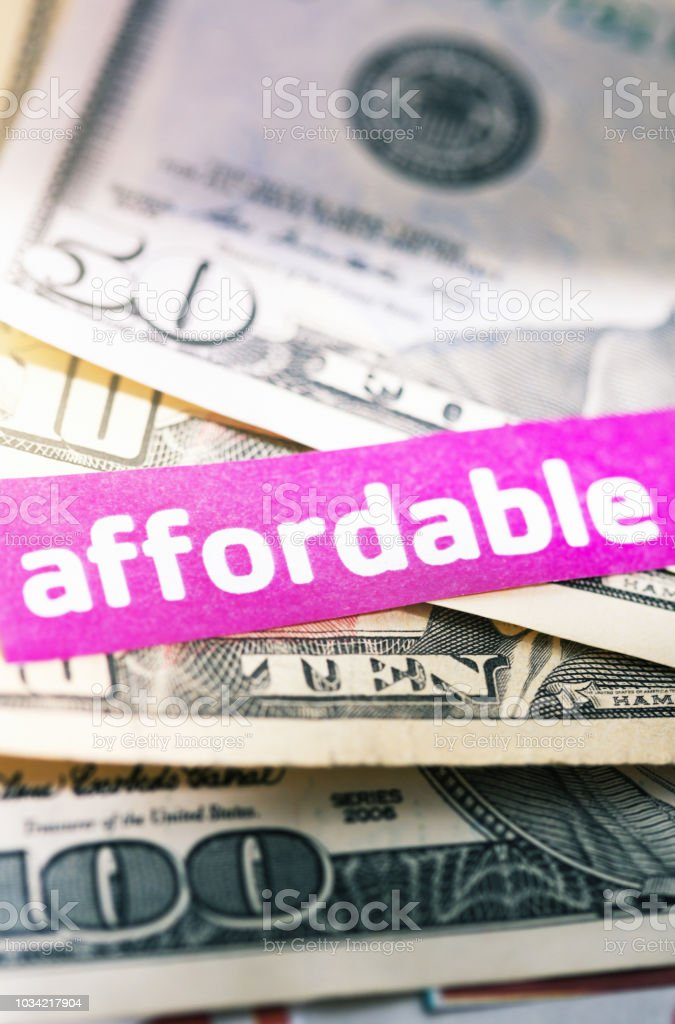 Stack of American banknotes with 'Affordable' sign stock photo