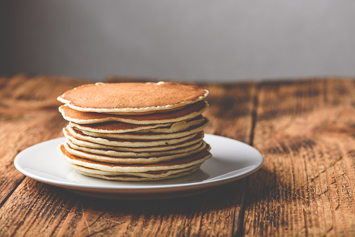 Stack of american pancakes on white plate