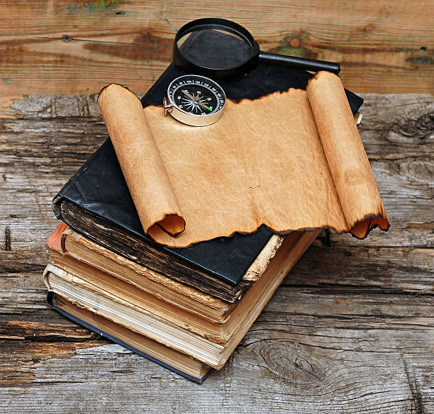 Stack of antique books with compass stock photo