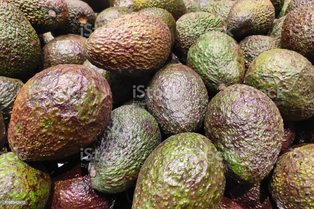 Stack of avocados on a market stall. Close-up on a stack of avocados on a market stall. Abundance Stock Photo