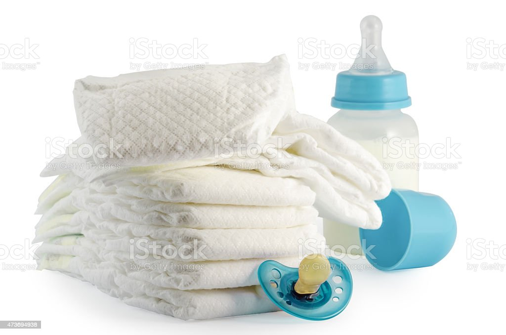 A stack of baby diapers bottle and a pacifier stock photo