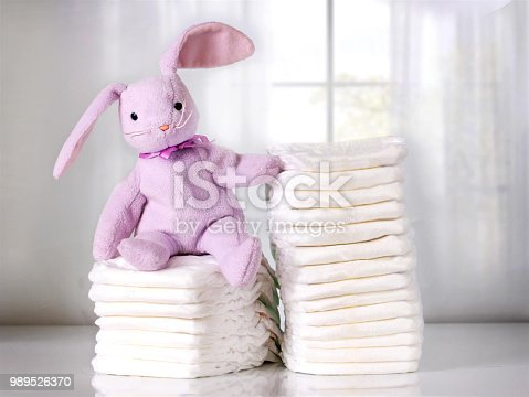 istock Stack of baby diapers on table with funny bunny. Bright background. 989526370