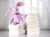 Stack of baby diapers on table with funny bunny. Bright background.