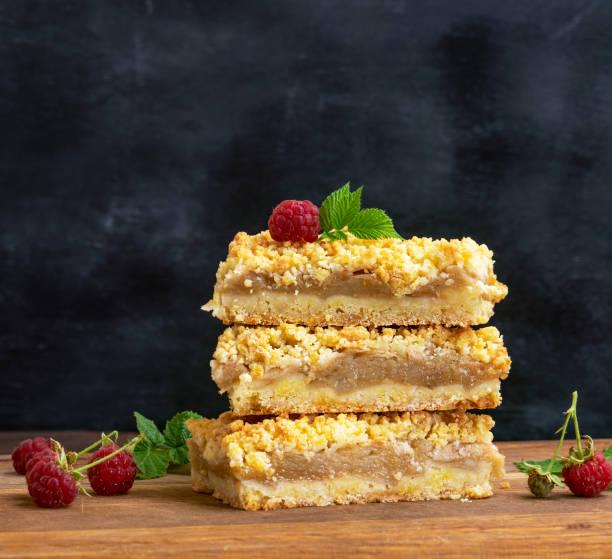 stapel von gebackenen scheiben kuchen mit äpfeln - himbeer crumble stock-fotos und bilder