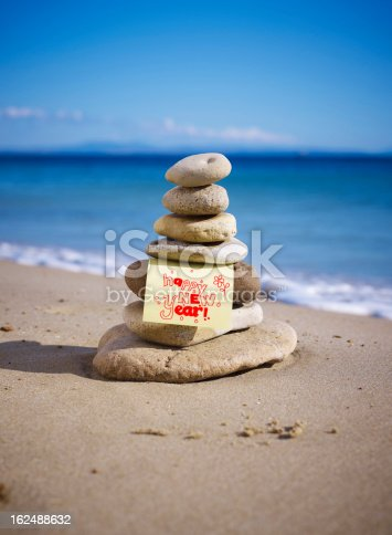 Zen stone little pile on beach. Background is slightly blurred. Nice bokeh. Paper note write a 2013