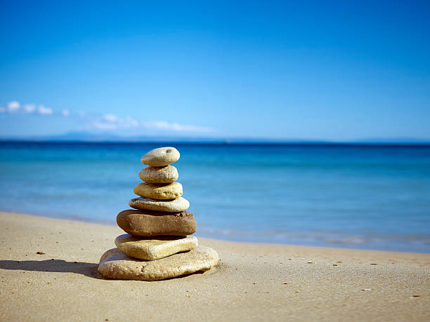 stack of balanced stones on the beach - stack rock stock pictures, royalty-free photos & images